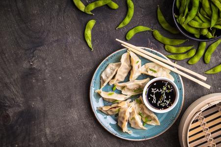 Chinese knoedels op plaat, groene gekookte sojabonen edamame, sojasaus en eetstokjesachtergrond. Traditioneel Chinees  Aziatisch gerecht. Dim sum dumplings klaar om te eten. Chinees keukenconcept. Ruimte voor tekst Stockfoto