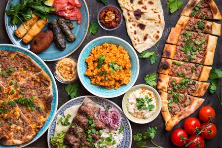 Traditionele geassorteerde Turkse gerechten. Turkse pizza, vlees kebab, pita, bulgur, gebakken gehaktballen, hummus en Turkse meze set. Diner in het Midden-Oosten. Feest van het eten. Turkse keuken. Bovenaanzicht. Oosters eten Stockfoto