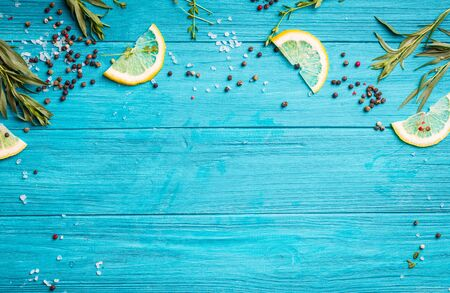 Food seasoning background. Blue coloured rustic wooden background, lemon slices, herbs, pepper, sea salt. Preparing a dinner. Space for text. Close-up. Vivid food frame. Top view. Cooking ingredients Фото со стока