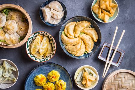 Surtido de aperitivos dim sum en el fondo rústico. Conjunto de comida china para compartir. Buffet asiático Comida china dim sum tradicional. Vista superior. Diferentes albóndigas y aperitivos chinos en la mesa Foto de archivo - 84059832