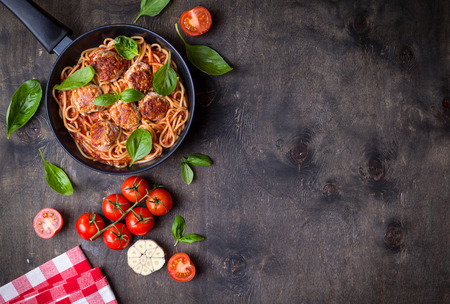 Spaghetti with meatballs, tomato sauce. Background. Italian American dish. Meatballs pasta in a pan. Space for text. Overhead. Traditional Italian cuisine. Dark rustic wooden table. Dinner with pasta Фото со стока