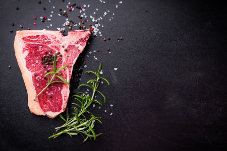 Raw marbled meat steak with seasonings on black chalkboard background. Space for text. Beef T-bone steak ready for cooking. Top view. Barbecue concept. Ingredients for meat roasting. Juicy meat steak