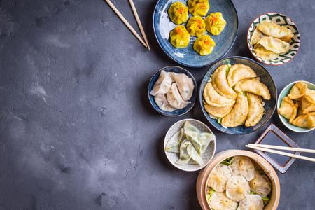素朴な背景に点心三種盛りの前菜。テキストのためのスペース。共有の中国の食糧。ビュッフェ式します。テキストのためのスペース。伝統的な中国の点心料理。平面図です。別の中国餃子と前菜 写真素材 - 84059861