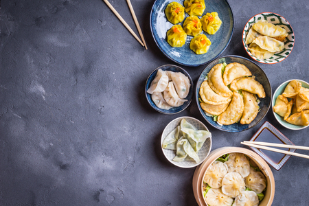Assorted dim sum appetizers on rustic background. Space for text. Chinese food for share. Buffet. Space for text. Traditional Chinese dim sum food. Top view. Different Chinese dumplings and appetizers Фото со стока