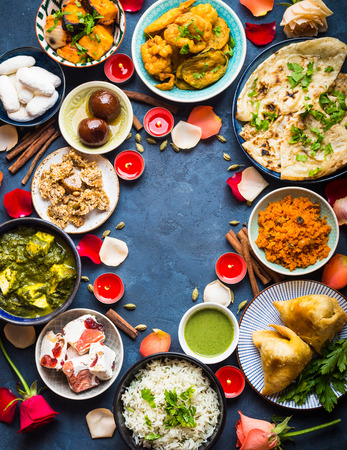 Festive food for Indian festival Diwali. Naan, samosa, rice, paneer, sweets. Background. Holiday Indian table with food, sweets, flowers, burning candles. Diwali celebratory dinner. Space for text.