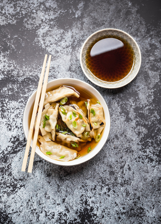 Asian dumplings in broth, bowl, chopsticks, soy sauce, rustic stone background. Top view. Chinese dumplings for dinner. Closeup. Traditional AsianChinese cuisine. Overhead. Soup Stock Photo