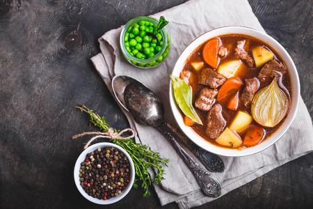 쇠고기, 감자, 당근, 양파, 향신료와 고기 스튜. 녹색 완두콩. 그릇, 나무 배경에서 천천히 요리 고기 스튜. 뜨거운 가을  겨울 요리. 닫다. 평면도. 텍스
