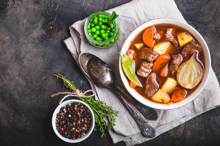 Meat stew with beef, potato, carrot, onion, spices. green peas. Slow cooked meat stew in bowl, wooden background. Hot autumn/winter dish. Closeup. Top view. Space for text. Comfort food. Homemade soup