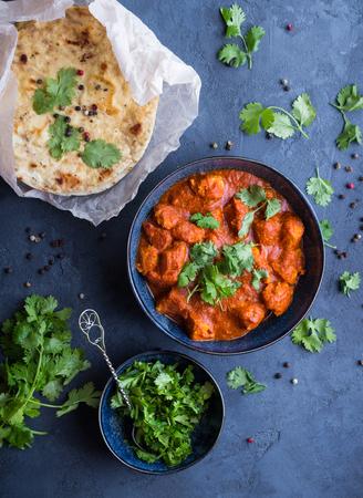 소박한 배경에 전통적인 인도  영국 요리 치킨 tikka masala. 매운 닭 tikka masala  카레에서 그릇, 인도 빵 naan, 실 란 트로. 인도식 저녁 식사. 닫다. 평면도.