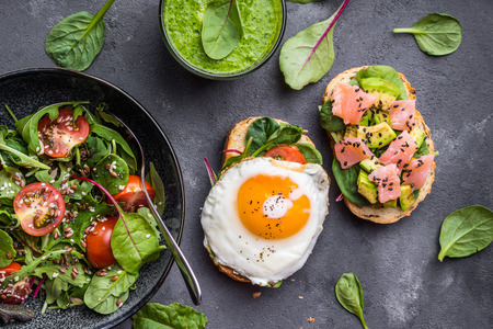 Fresh healthy dinner. Vegetable salad, sandwiches with fried egg and salmon, fresh green smoothie. Healthy eating concept. Detox dietplan. Top view. Weight loss. Healthy food program. Clean eating