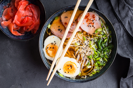 Traditional Japanese soup ramen with meat broth, asian noodles, seaweed, sliced pork, eggs and ginger on dark concrete background. Close up. Asian style food. Top view. Hot tasty ramen soup for dinner