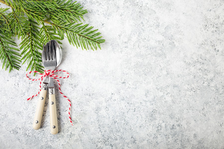 94044917 christmasnew year background christmas table place setting festive dinner background spoon fork fir branch on white concrete background