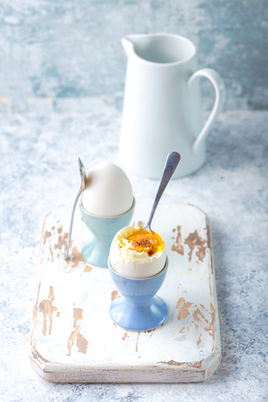 Fresh soft boiled eggs in stands, spoons, white wooden cooking board, white concrete rustic background. Soft eggs for healthy breakfast. Jar with milk. Selective focus. Egg protein fitness breakfast