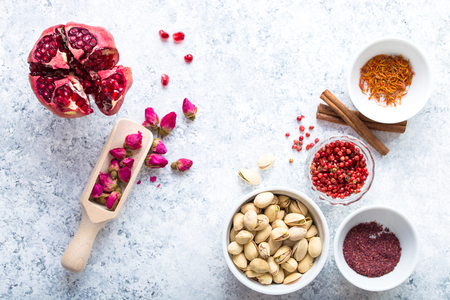 Arab ingredients, middle eastern food. Space for text. Arabic cuisine ingredients, white concrete background. Rose buds, spices, pomegranate, pistachios. Halal food making. Top view. Arab food concept