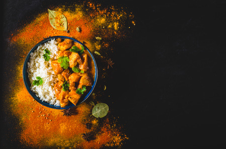 Indian Butter chicken with basmati rice in bowl, spices, black background. Space for text. Butter chicken, traditional Indian dish. Top view. Chicken tikka masala. Indian cuisine concept. Overhead 스톡 콘텐츠
