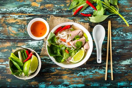 Traditional Vietnamese soup Pho bo with herbs, meat, rice noodles, broth. Pho bo in bowl with chopsticks, spoon. Space for text. Top view. Asian soup Pho bo on wooden table background. Vietnamese soup