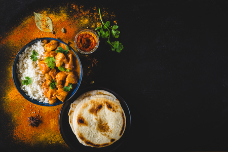 Indian Butter chicken with basmati rice in bowl, spices, naan bread. Black background. Space for text. Butter chicken, traditional Indian dish. Top view. Chicken tikka masala. Indian cuisine