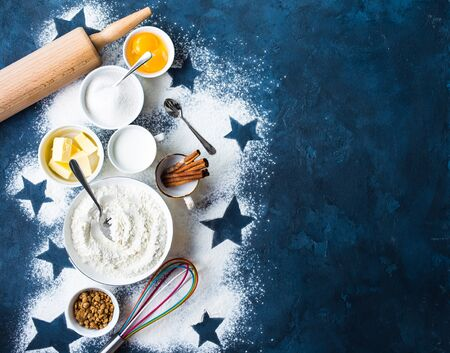 Baking background. Flour, white, brown sugar, eggs, butter, milk, cinnamon sticks, whisk, rolling pin. Ingredients for baking. Kitchen utensils. Space for text. Top view. Making baked goods. Concept Stock Photo