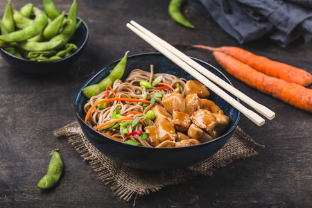 Asian noodles with chicken, vegetables in bowl, rustic wooden background. Soba noodles, teriyaki sauce chicken, edamame beans, sesame, chopsticks. Closeup. Asian style dinner. ChineseJapanese noodles