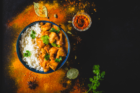 Indian Butter chicken with basmati rice in bowl, spices, black background. Space for text. Butter chicken, traditional Indian dish. Top view. Chicken tikka masala. Indian cuisine concept. Overhead Standard-Bild