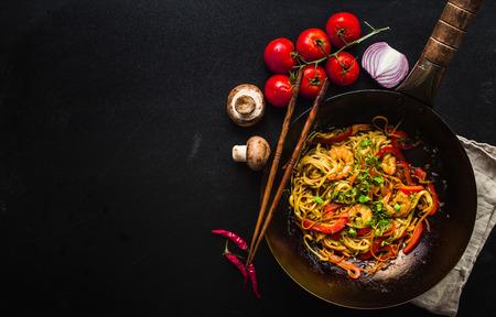 Rühren Sie braten Nudeln im traditionellen chinesischen Wok, Stäbchen, Zutaten. Platz für Text. Asiatische Nudeln mit Gemüse, Garnelen. Wok-Nudeln. Schwarzer dunkler Hintergrund. Ansicht von oben. Asiatisches / chinesisches Abendessen