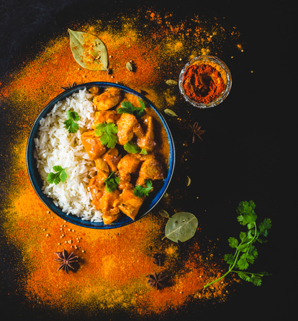 Indian Butter chicken with basmati rice, bowl, spices, black background. Indian style dinner. Butter chicken, traditional Indian dish. Top view. Chicken tikka masala. Indian cuisine concept. Overhead