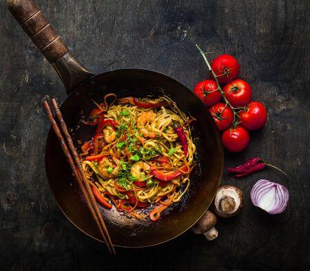 Stir fry noodles in traditional Chinese wok, chopsticks. Asian noodles with vegetables, shrimps. Wok noodles, Chinese dinner/lunch. Black dark background. Top view. Asian/Chinese noodles. Stir frying