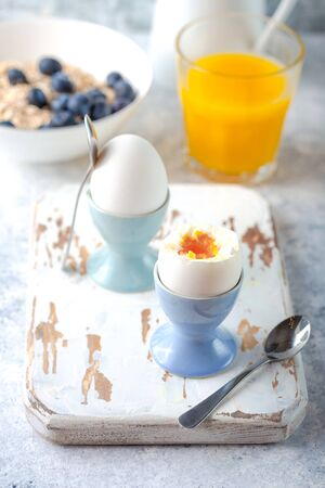Fresh soft boiled eggs, oatmeal with blueberries, coffee, orange juice, milk. White concrete rustic background. Soft eggs, healthy breakfast. Selective focus. Tasty light fitness breakfast. Closeup Stock Photo
