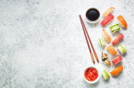 Assorted sushi set on white concrete background. Space for text. Japanese sushi, rolls, soy sauce, ginger, chopsticks. Top view. Sushi nigiri. Japanese dinner/lunch. Food frame. Different sushi mixed Standard-Bild