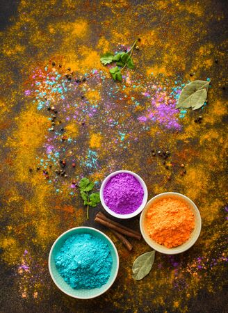 Traditional Indian Holi colours powder, spices, rustic background. Indian Holi holiday. Holi celebration. Top view. Festive Indian table setting. Space for text. Holi concept. Decoration with paints  Reklamní fotografie