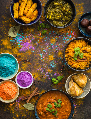 Traditional assorted Indian food, Holi colours powder, rustic background. Indian Holi holiday. Indian dishes and snacks set. Holi celebration. Top view. Festive Indian table setting. Space for text Stock Photo