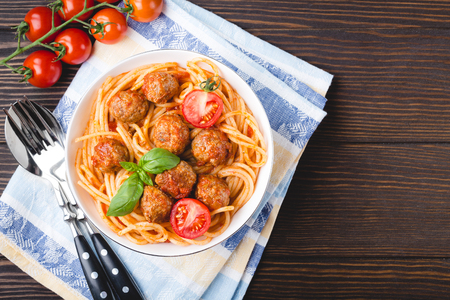Italian American traditional dish spaghetti with meatballs, tomato sauce and basil in bowl, rustic wooden background, top view, copy space. Close-up of meatballs pasta Reklamní fotografie