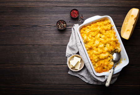 Close-up of baked macaroni and cheese in white casserole on wooden background, with seasonings, butter, spoon and fork, top view, space for text. Pasta with cheesy sauce, AmericanEnglish comfort food