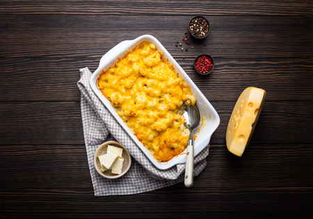 Close-up of baked mac and cheese in white casserole on rustic wooden background, with seasonings, butter, spoon and fork, top view. Pasta with cheesy sauce, AmericanEnglish comfort food