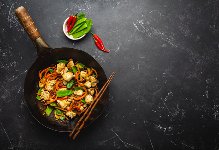 Rühren Sie Hähnchen mit Gemüse in alter rustikaler Wokpfanne, Stäbchen auf schwarzem Steinhintergrund, Nahaufnahme, Draufsicht. Traditionelles asiatisches/thailändisches Essen, Platz für Text