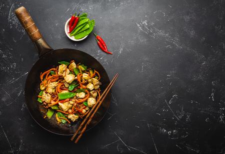 Sauté de poulet aux légumes dans une vieille poêle à wok rustique, baguettes sur fond noir en pierre, gros plan, vue de dessus. Repas traditionnel asiatique/thaï, espace pour le texte