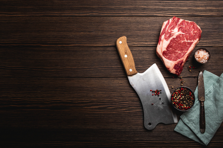 Top view of raw fresh marbled meat steak Ribeye, rustic meat cleaver, seasonings on wooden background with space for text. Cooking juicy organic steak/butchery concept, healthy clean eating, close up 免版税图像 - 117976291