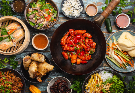 Set of assorted Chinese dishes on table: sweet and sour chicken in wok pan, dim sum in bamboo steamer, spring rolls, noodles, salad, rice, steamed buns, dips. Asian style dinner or buffet, top view