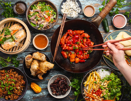 Set of assorted Chinese food on table with female hand holding chopsticks from above. Full and festive table with all traditional Chinese dishes, asian style dinner or buffet, top view 