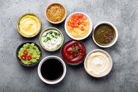 Set of different sauces in bowls on gray rustic concrete background, top view, close-up. Tomato ketchup, mayonnaise, guacamole, mustard, soy sauce, pesto, cheese sauce - assortment of dips
