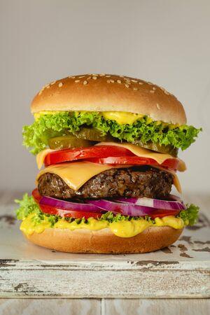 Deliciosa hamburguesa con carne, queso derretido, salsa que gotea y verduras sobre fondo blanco rústico. Sabrosa hamburguesa recién hecha, primer plano. Foto de archivo