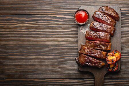 Bistecca di carne marmorizzata alla griglia/fritta e affettata con forchetta, pomodori, salsa di pomodoro/ketchup su tagliere di legno, vista dall'alto, primo piano con spazio per il testo, sfondo rustico. Concetto di bistecca di carne di manzo