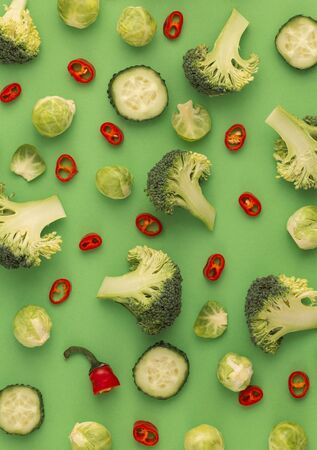 Colourful vegetables food pattern made of broccoli, Brussels sprouts, cucumber, chili pepper, green background. Minimal flat lay design about nutrition, healthy eating, diets, vitamins. Top view