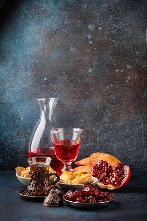 Ramadan kareem Iftar evening meal with dates, baklava, traditional Arabic sweets, fruit, Arab tea, rose sherbet beverage in glass jug. Islamic festive decorated dinner, Ramadan food composition .