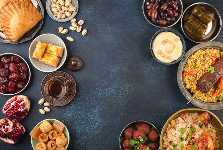 Ramadan kareem Iftar party table with assorted festive traditional Arab dishes, sweets, dates. Eid al-Fitr mubarak evening grand meal, top view. Islamic holidays food, Ramadan feast, space for text. Banque d'images