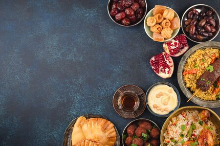 Ramadan kareem Iftar party table with assorted festive traditional Arab dishes, sweets, dates. Eid al-Fitr mubarak evening grand meal, top view. Islamic holidays food, Ramadan feast, space for text.