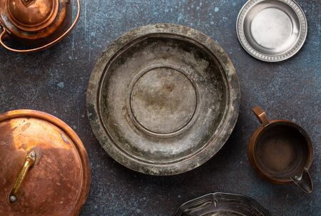 Close up of old vintage nickel silver empty plate, rustic concrete background, space for text. Antique utensils: pan, plates, teapot. Aged retro copper and aluminum cookware, from above. Stockfoto