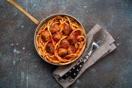 Overhead of traditional homemade pasta with roasted meatballs, tomato sauce in copper vintage pan with fork and knife on rustic concrete background. Classic homemade meatballs spaghetti for dinner Zdjęcie Seryjne