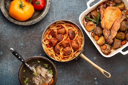 Dining table with traditional tasty homemade dishes: chicken soup, meatballs with spaghetti, roasted chicken with potatoes. Classic home natural comfort food for family meal dinner, top view