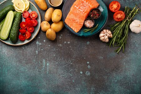 Raw salmon fish fillet, fresh vegetables, herbs - ingredients for cooking healthy meal. Natural clean organic healthy food selection on concrete background, dieting and nutrition, copy space, top view
